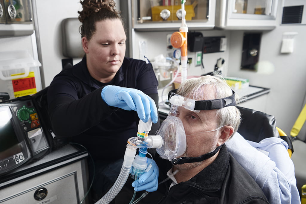 The photo shows a patient getting a nebulizer via CPAP.