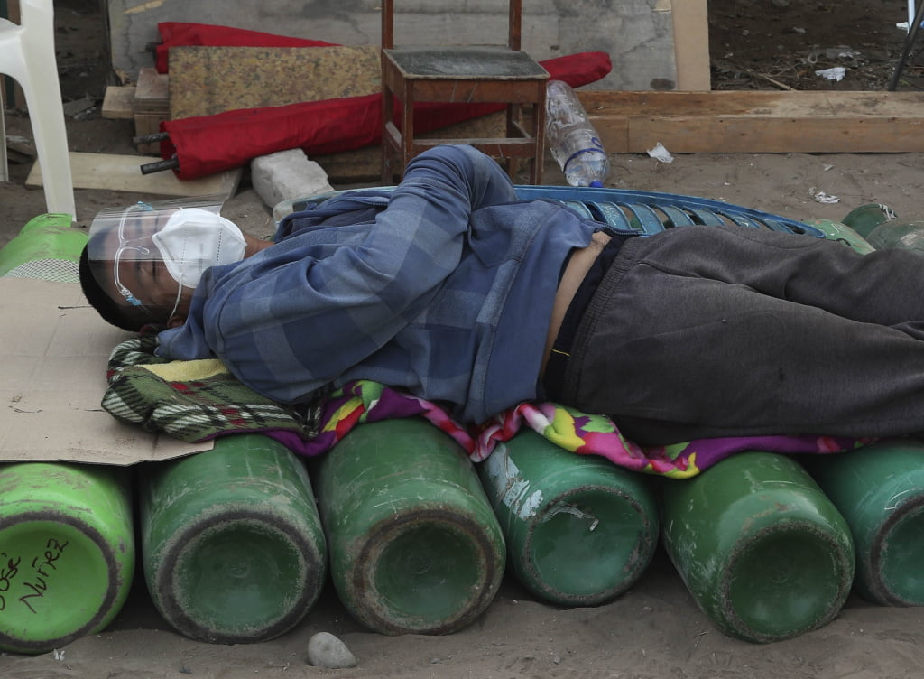 A man sleeps on top of empty oxygen cylinders, waiting for a shop to open to refill his tank, in the Villa El Salvador neighborhood of Lima, Peru, early Thursday morning, Feb. 18, 2021. A crisis over the supply of medical oxygen for coronavirus patients has struck nations in Africa and Latin America, where warnings went unheeded at the start of the pandemic and doctors say the shortage has led to unnecessary deaths.